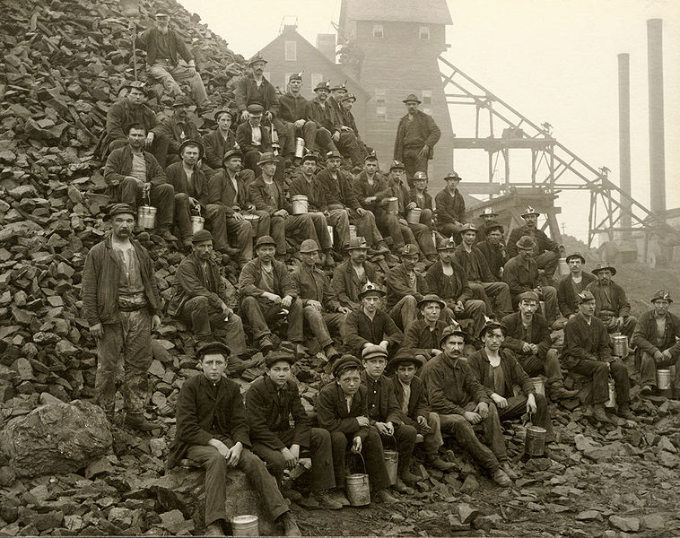 "Upper Peninsula Michigan, USA, 1905. Miners pose with lunch pails in hand on a pile of ""poor rock"" (waste rock) outside of the Tamarack mineshaft. In the background is the Tamarack #5 Shaft-Rockhouse. This mine was one of the most productive mines in Copper Country. (Source: Public domain. Courtesy of Keweenaw National Historic Park Archives)"